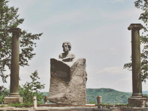 Granite statue of Hephaestus, the Greek god of fire, metalworking, stone masonry, forges and the art of sculpture - located at the Grand Overlook at Millstone Trails in Barre VT.